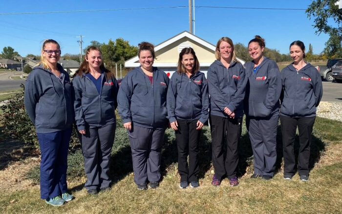 staff at animal doctor in junction city, KS posing in front of the building sign